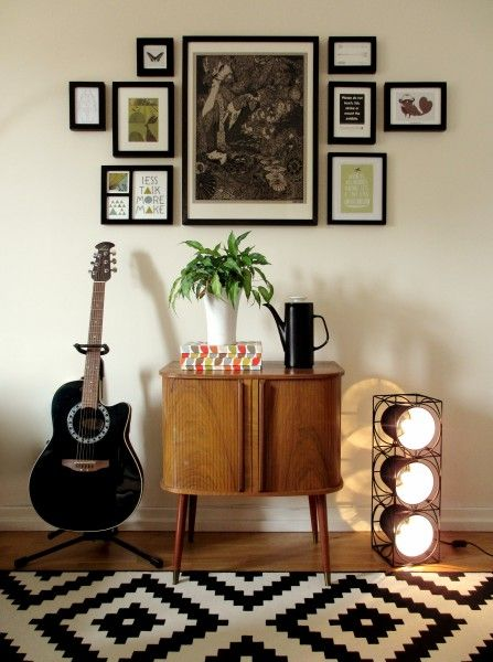 Lucy's monochrome hallway with a guitar, picture wall, bright plant and t he Bowie Table Lamp in Black. | MADE.COM/Unboxed