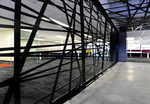 Perete metalic din tabla de otel traforat sub forma unei panze de paianjen cu aspect de paravan interior