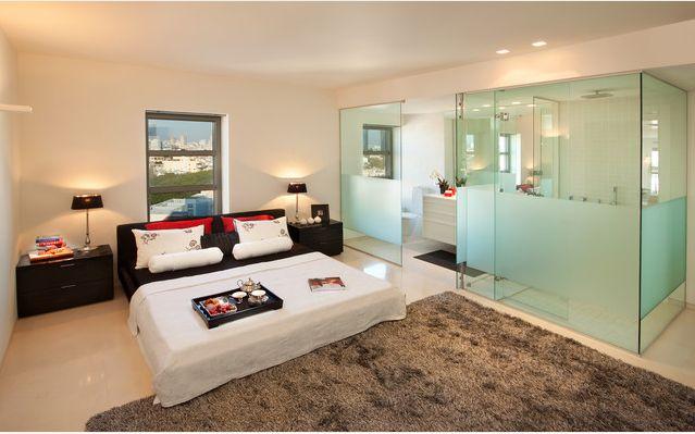 Banheiro integrado ao quarto através de 'paredes de vidro'