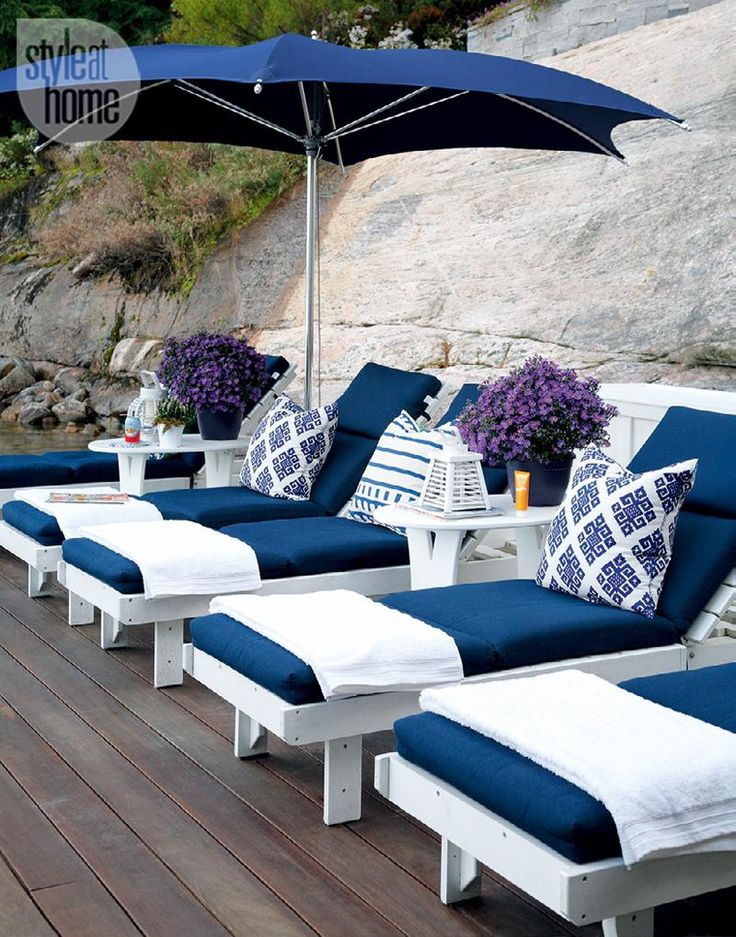 The dreamy dock—The blue and white scheme is carried from the main cottage exterior to the boathouse and the dock furnishings.