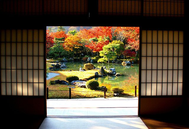 Traditional Japanese room framing view of garden in Autumn.  Love the contrast between the dark linear and vibrant natural colors outside.