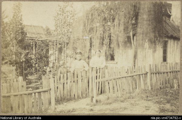 Sarah Ellis, nee Gudgeon, another woman and a young boy, standing at the paling fence in the garden of the Ellis residence, a slab hut with...