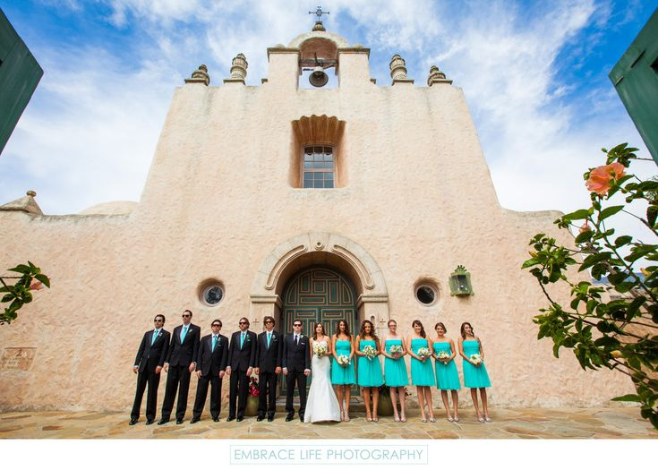 Embrace Life Photography - Our Lady of Mount Carmel Church Wedding Party Portrait: Couple and their wedding party stand in front of uniquely Southwestern architectural style church in Montecito, Santa Barbara church wedding ceremony location. The early 20th century historic site is beautiful mission-style architecture in contrast to the teal contemporary style wedding party. Our Lady of Mount Carmel Church is located in Santa Barbara, CA. Phone: (805) 969-6868. Website…