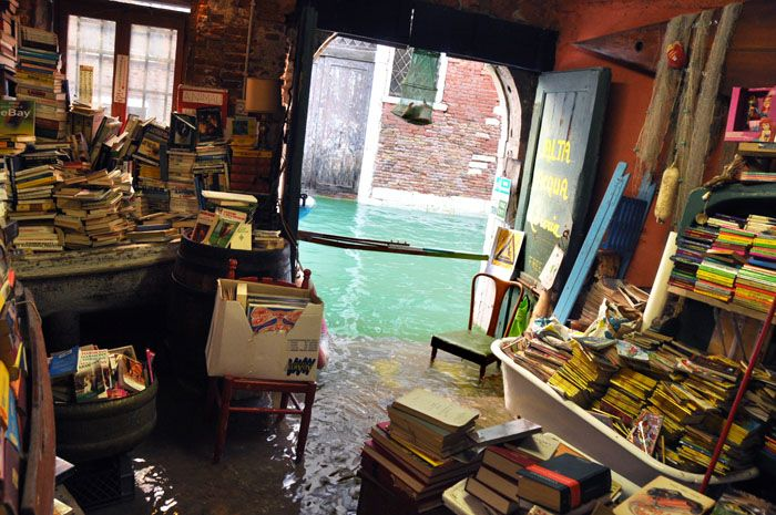 """The famous Venetian """"Libreria Acqua Alta"""" is one of the most original book shops in the world, with its true gondola in the center, to display books on.  What you see on this picture is just the back of the shop, where are displayed comics and old books. Those days, the book shop fully deserves its name!"""