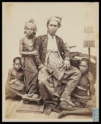 1865 Ketut Djelantik with The Princess Gusti Ajoe Putu on his arm. You can see the King's foot rests firmly on the girl holding the umbrella. This is to signify he is above her and in control of her. In Indonesian culture the feet are considered unclean and one should never point with the foot, step over someone or touch someone with thier foot. Here the King makes a clear statement that this is my daughter, The Princess, elevated on a stool and even with The King and below us are our…