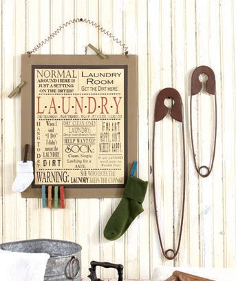 The Laundry Room Wall Decor adds a fun twist to this never-ending chore. The Set of 2 Safety Pins is a cute addition to any country decorating plan. Rustic bronze finish gives the metal pins an antique look. Display them open or closed. The Wall Board (1