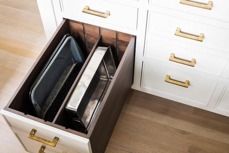 White kitchen island boasts drawers donning antique brass pulls and a custom baking pan drawer finished with dividers.