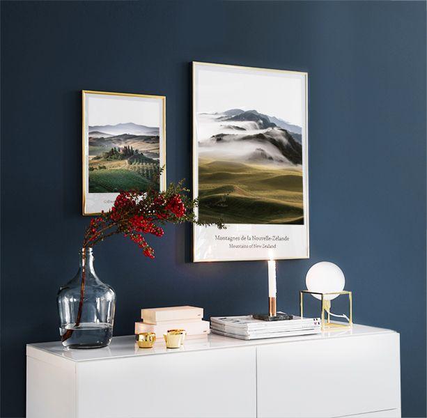 Tavelvägg / tavelcollage ovanför vit sideboard. Snygga posters och prints med naturmotiv i guldram. Vacker mörkblå väggfärg mot det vita.