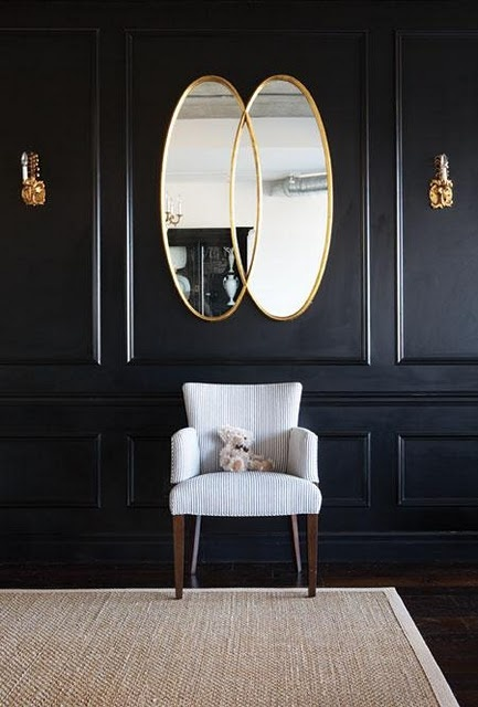 classic panelled living room with black walls, double oval mirror and white furniture