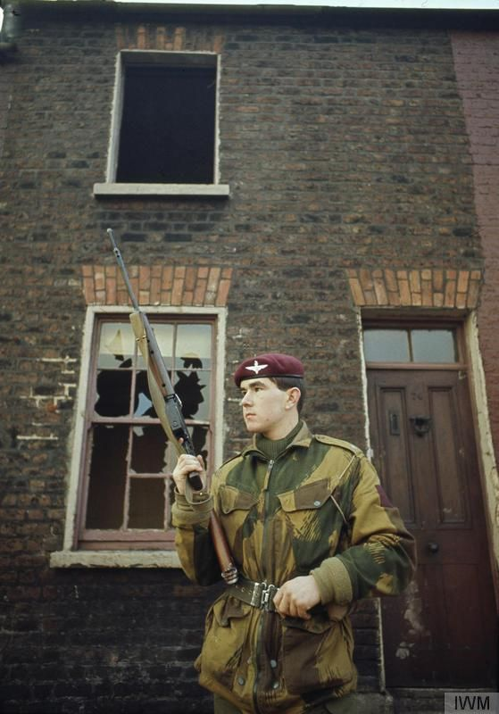 2nd Lieutenant David Brough, 1st Battalion, The Parachute Regiment, patrols with his rifle in front of a derelict house in Belfast.