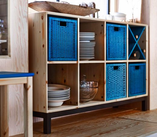 Banco em pinho maciço com compartimentos onde estão cestos de rota em azul