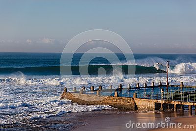 Winter morning ocean waves of good shape crashing surging onto shallow reefs in front of concrete tidal pool.