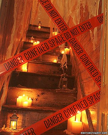 """Haunted House Party  Spooky Stairwell  Add fireproofed curtains, clusters of candles, and police tape to cordon off the stairs to the private rooms of the house.    Manny says"""" pretty cool for those who have stairs. Not only a party, but for Halloween night. When you open the door vistors can see the creepy backdrop."""