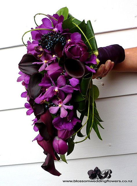 Callas, tulips, orchids, berries, & vines wrapped in dark purple satin.... love this, but not digging the shape... Also, the title of this article is very misleading.