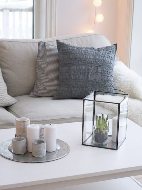 Gray and white. String lights. Coffee table with plate of candles and plant enclosed in lantern. <3