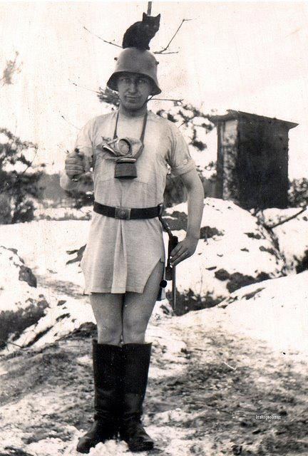 German soldier with a cat on his head while wearing a nightshirt, a helmet, boot, armed with a bayonet, and standing in front of a latrine.