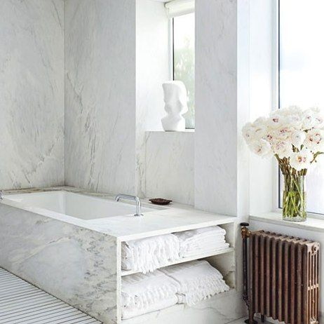 The master bath is equipped with a Kohler tub; the fittings are by Lefroy Brooks, with a orange hand shower by Agape, and the towels are by ...