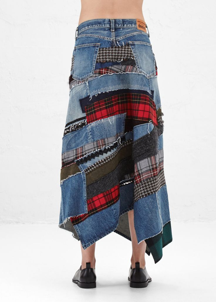 Asymmetrical midi skirt in washed blue cotton denim with multi-colored patchwork attachments throughout. Straight fit at waist. Button fly and closure. Classic five-pocket styling. Dry clean only.