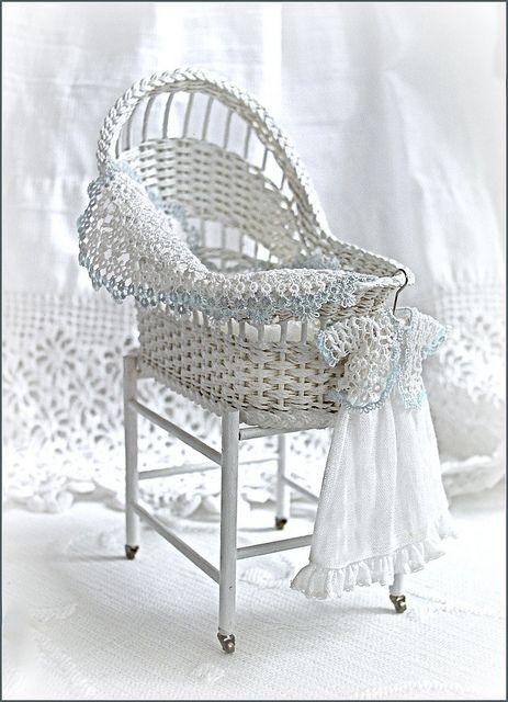 1:12th scale miniature wicker bassinet by Carolyn Lockwood .