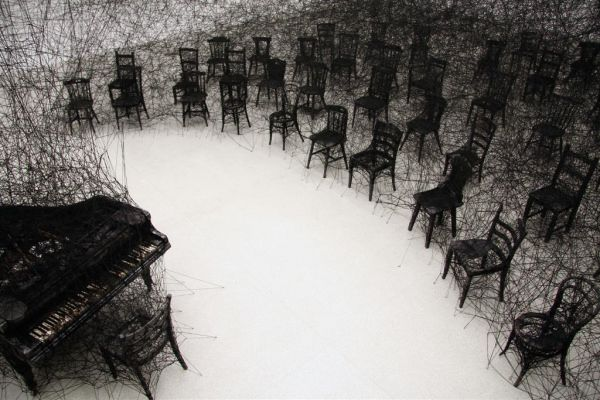 Though the piece echoes sketch-like imagery, it is in fact an installation piece involving a burnt piano in a room ravaged by black wool.   In Silence by Chiharu Shiota