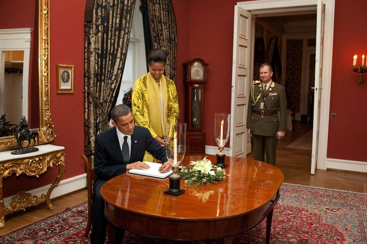 President Barack Obama and First Lady Michelle Obama sign the guest book at Slottet Royal Palace of Norway in Oslo, Norway, Dec. 10, 2009. (Official White House Photo by Pete Souza)  This official White House photograph is being made available only for publication by news organizations and/or for personal use printing by the subject(s) of the photograph. The photograph may not be manipulated in any way and may not be used in commercial or political materials, advertisements, emails, prod...