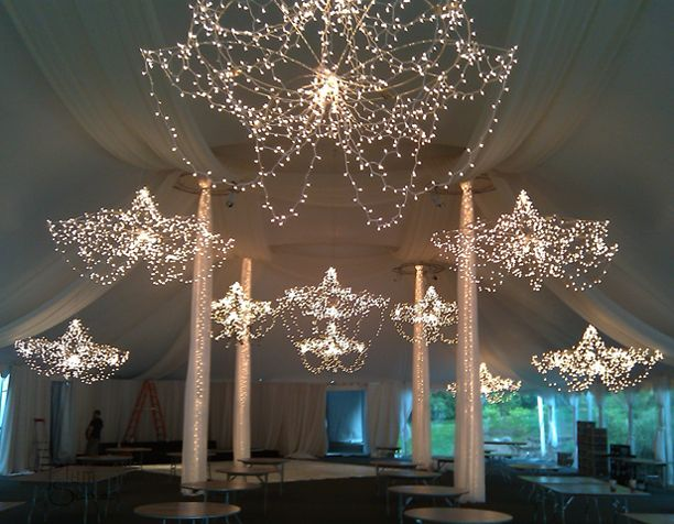 """Tent decorated with custom """"chandeliers"""" created from a combination of tiny lights and lucite rods."""