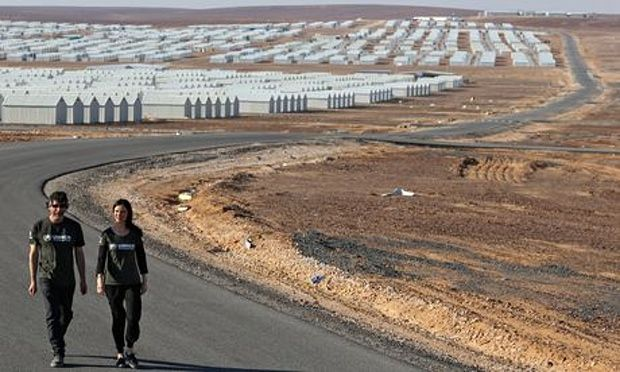 'A ghost city of white boxes' … Neil Gaiman and Georgina Chapman outside Azraq camp.