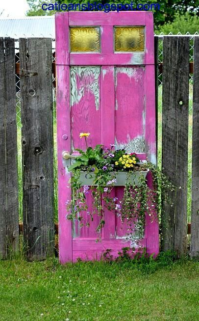 this old door painted this incredible color simply has a window box attached to the front, and is used as art in the garden.