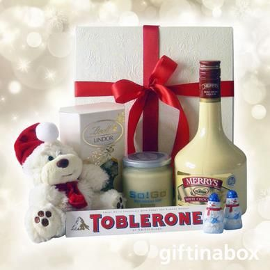 Dreaming of a white Christmas? This is the perfect hamper to make your dreams come true! A selection of delectable white chocolate, cream liquer, and a Christmas teddy, all presented in a white box with red ribbons and bows   Merry's white chocolate cream liqueur Toblerone 100g chocolate bar 2 x Lindt Lindor chocolate snowmen Lindt Lindor white chocolate box White chocolate sauce Christmas teddy bear