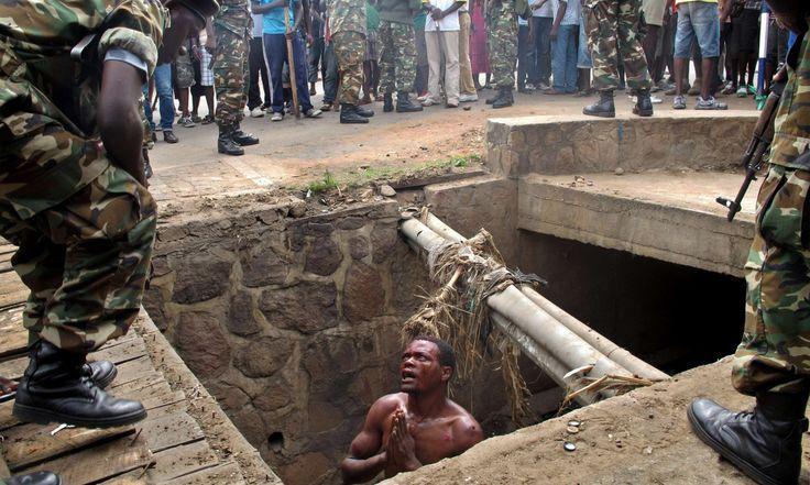 SALVADO POR EL EJERCITO EN BURUNDI. Un hombre pide la ayuda a  militares desde una cuneta donde se escondió el 7 de mayo de 2015 para  escapar de un seguro linchamiento a manos de una turba en el distrito  Cibitoke, en Bujumbura, capital de Burundi. El hombre sospechoso de ser  un 'Imbonerakure', o miembro de la Liga de la Juventud del partido  gobernante de Burundi finalmente fue salvado por el ejército. Al menos  tres personas murieron en enfrentamientos en Burundi durante protestas…