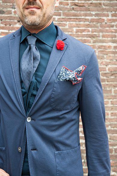 2015S/S ピッティ・ウォモ スナップ(1) ジャケットの小物使いで華やぎを バラをモチーフにした深紅のラペルピン、そしてネイビーの総柄に赤で縁取りを加えたチーフが着こなしを華やかな雰囲気に。ス・ミズーラで仕立てたシャツとタイの色合わせも美しく、シャツにタイをインしているのもイタリア的。