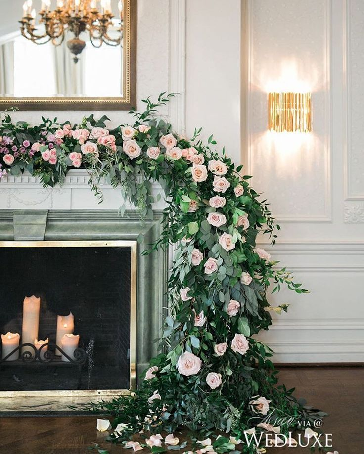 A garland of greenery and pale pink roses draped over a fireplace mantle serves as a dreamy #ceremony backdrop- the perfect setting for #fairytale-worthy #IDos!