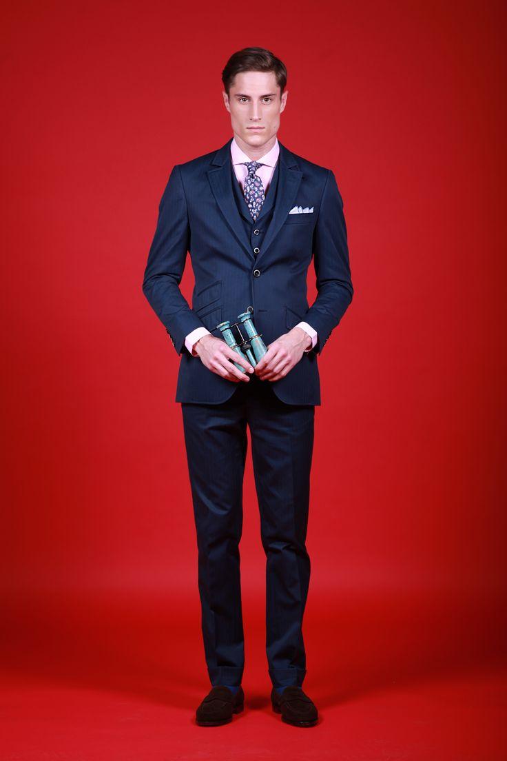 Costume en coton bleu marine, tissu à chevrons. Veste Kensignton à deux boutons : coupe anglaise cintrée, poches en biais avec petite poche ticket, de vraies boutonnières aux manches. Pantalon coupe slim sans pince et braguette à zip, avec passants de ceinture et side ajusteur.