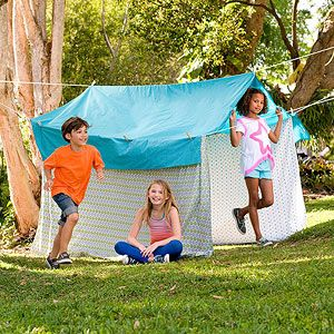 Pitch this easy tent to create a backyard summer camp! All you need: clotheslines, sheets, and clothespins.