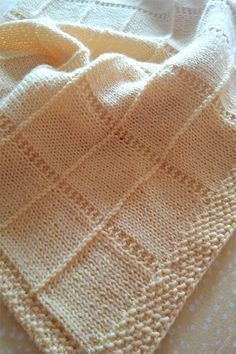 Free knitting pattern for Dreambaby Baby Afghan - JoAnne Turcotte designed this easy yet beautiful blanket with squares bordered by purl and garter stitch ridges. Four sizes, from doll size to crib size. Pictured project is by assia90