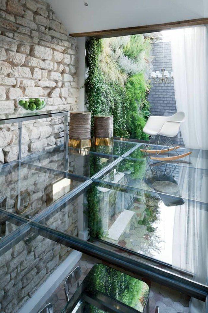 une belle chaise berçante en plastique blanc, sol en verre transparent, fenetre grande