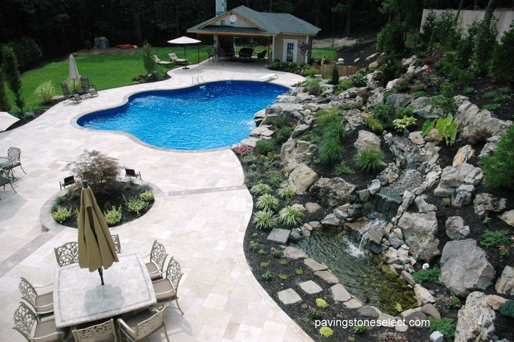 the travertine natural paving stone walkway  in a beautiful hand crafted London pattern design for surrounding the swimming pool, cabana, masking the huge waterfall on hill, and the layers of the multi-leveled water runoff completed with individual sections of properly placed natural stones from our endless variety. Complied by laying out the correct soil, installing each flower and plant in its rightful location, making sure the natural stones are hugging the waterfall throughout the hill.