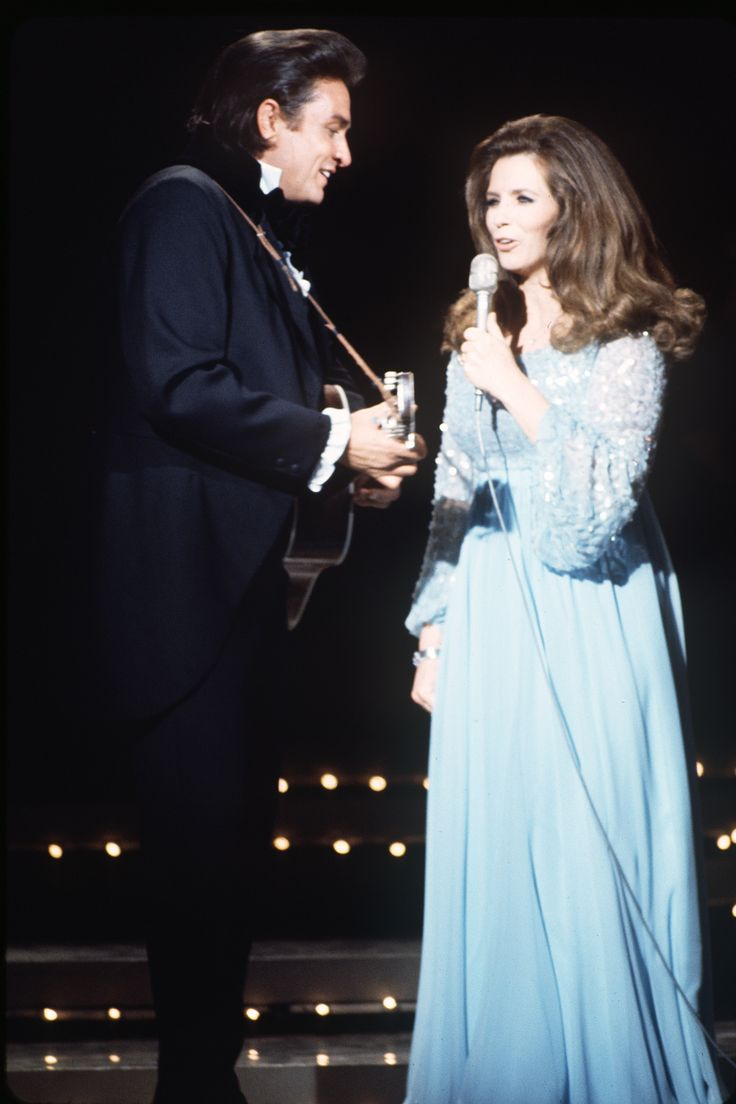 """June Carter was born into a musical family, performing with the Carter Family as early as age 10. She met singer Johnny Cash in 1950 backstage at the Grand Ole Opry, their first duet came in 1964 with """"It Ain't Me Babe."""" The two performed together for years before Cash proposed in front of a live audience in 1968. - HarpersBAZAAR.com"""