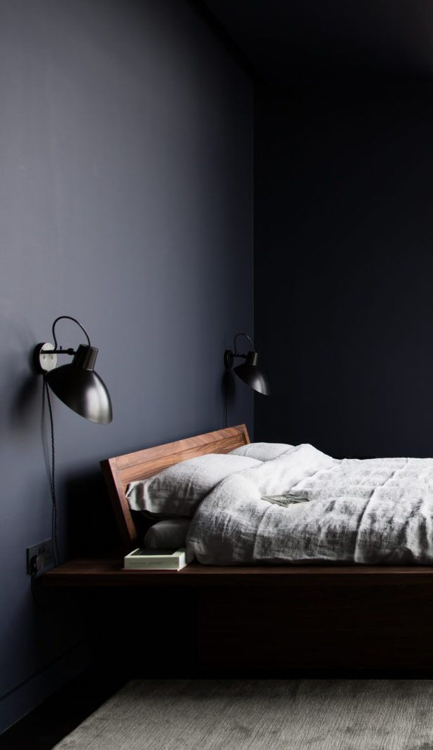 Minimal bedroom home decor painted dark navy almost black walls with simple gray linen bedding.