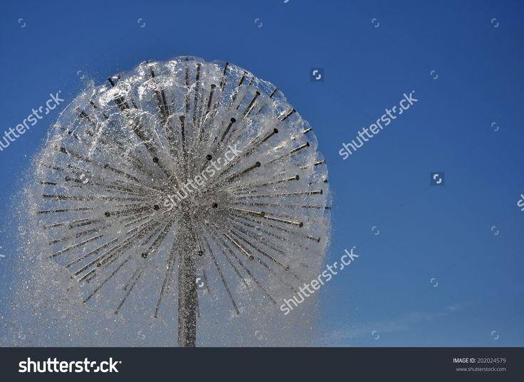 Dandelion-like fountain over blue sky