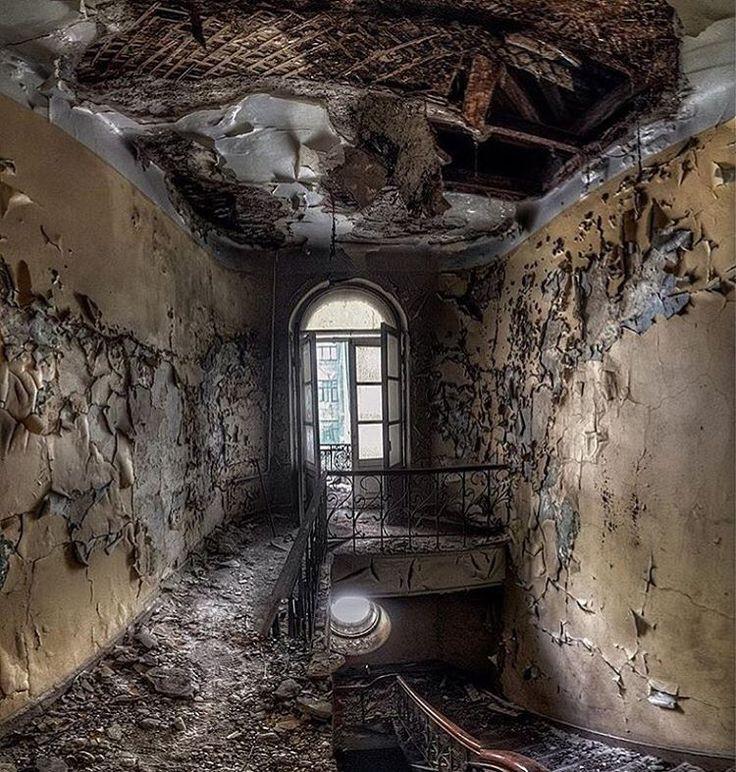 Afbladderende verf op de muren, puin op de vloer en een gat in het dak