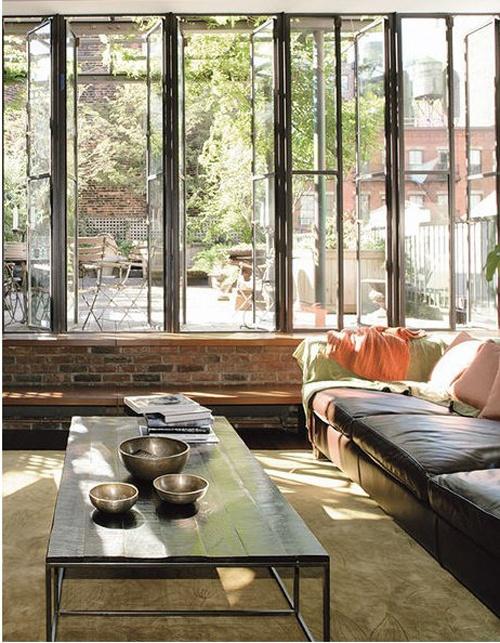 Un loft aux murs de briques à Soho dreamy low key lounge room with darling courtyard  and bank of windows low sofa low coffee table