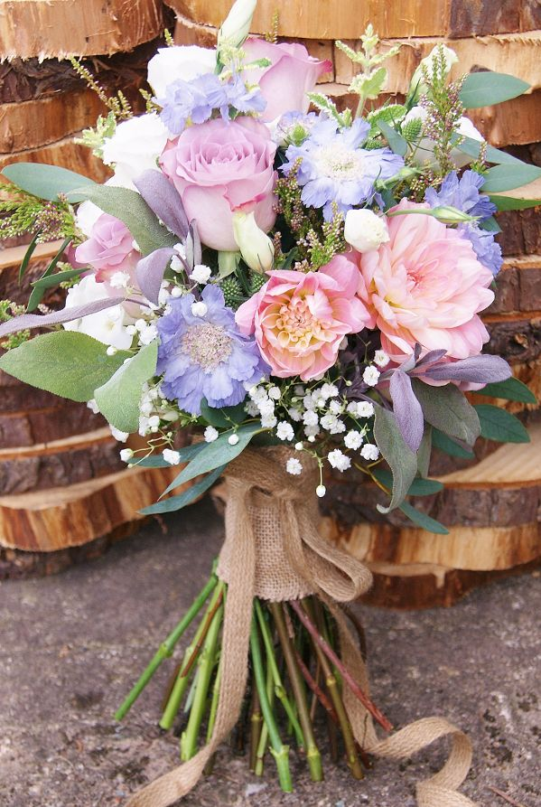Florissimo, Shropshire - Flowers for weddings, events and businesses. Hand-tied bridal bouquet of mauve memory lane roses, British pink dahlia, British mauve scabious, white British white lisianthus, British white eryngium thistle, British pink heather, gypsophila and British herbs. At Pimhill Barn