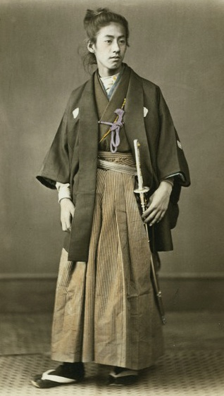 Young man - Prince Okundaira - in formal haori. Hand-colored photo, 1870's, Japan, by photographer Felice Beato.