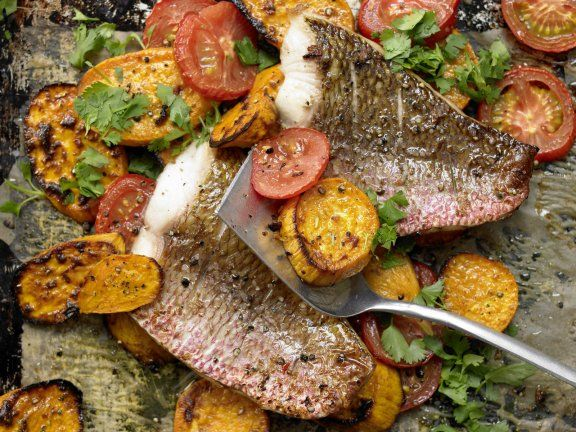 Cooked on one pan, this baked red snapper is paired with warming spices, tomatoes, and sweet potatoes.