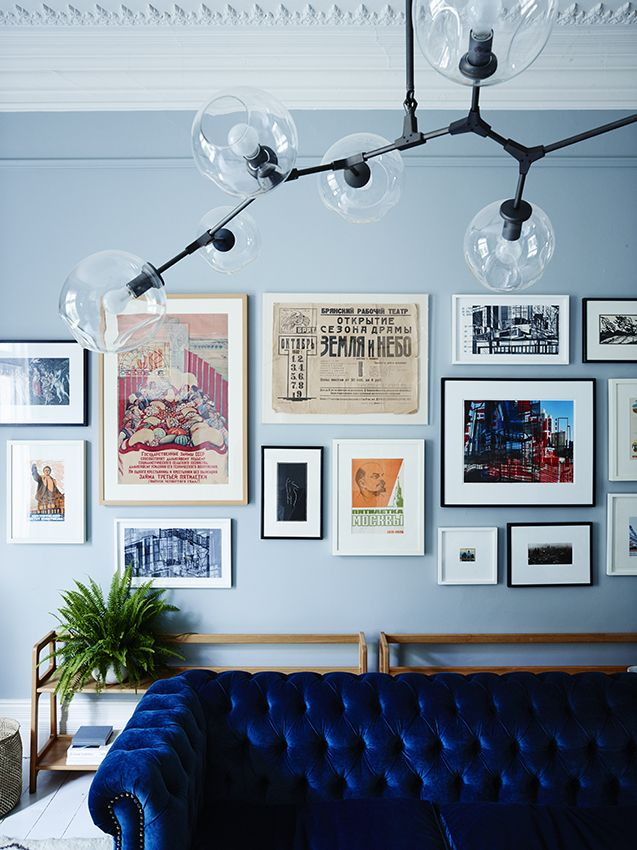 Love the pale blue walls against the navy blue velvet chesterfield sofa. And that gallery wall is phenomenal.