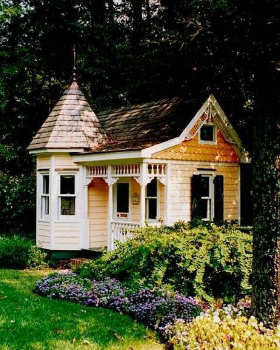 Cute little victorian playhouse. Perfect in this spot. Love the porch details.