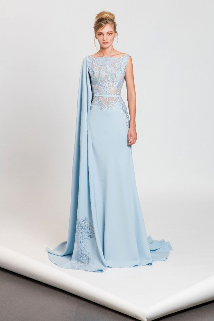 Light blue dress in Moroccan crepe and laser cut embroidered tulle featuring a one sided embroidered cape and a belt on the waistline.