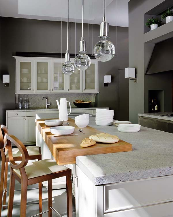 I love the mix of the raw concrete countertops with the warm wood knife block / eating tray sat on top