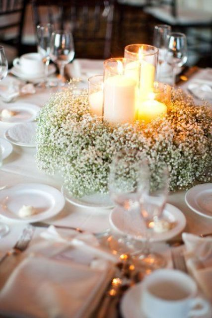 a baby's breath wreath with candles in tall glass candle holders